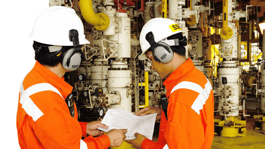 Workers operating machinery on an oil rig.