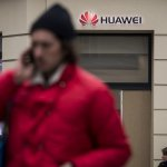 People pass by a Huawei logo above the entrance of a Huawei store in Paris