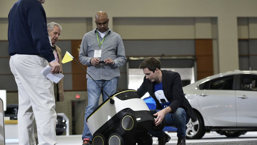 Henry Harris-Burland (R) explains the operation of the Starship Technologies delivery robot