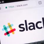 Slack website displayed on smartphone hidden in jeans pocket