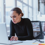 woman using laptop while sitting at her desk. Young african american businesswoman sitting in the office and working on laptop